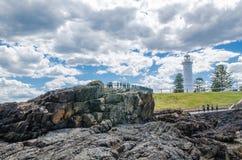 Felsige Küstenansichten mit ikonenhaftem Leuchtturm am Luftloch zeigen, südlich Kiama-Hafens, am Tag des bewölkten Himmels lizenzfreie stockfotos