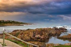 Felsige Küstenlinie auf dem Ozean bei De Kelders, Südafrika, berühmt für das Walaufpassen Wintersaison-, bewölkter und drastische stockfoto
