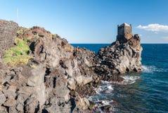 Felsige Küstenlinie der Lavaklippe nahe Acireale Sizilien, mit einem Wachturm im Hintergrund Stockfotos