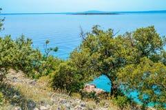 Felsige Küstenlinie mit Büschen und Olivenbäumen durch das adriatische Meer Lizenzfreies Stockfoto