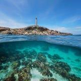 Felsige Küstenlinie mit einem Leuchtturm und einem Meeresgrund mit Felsen und einem Sand Unterwasser stockfotos