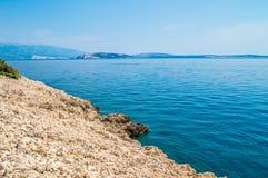 Felsige Küstenlinie mit haarscharfem blauem adriatischem Meer mit Insel Stockfoto