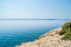 Felsige Küstenlinie mit haarscharfem blauem adriatischem Meer mit Insel Stockfotografie