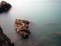 Felsige Küstenlinie mit Möve und versenkten Felsen, seidiges Wasser Stockfotos
