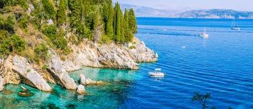 Felsige Küstenlinie umfasst durch Zypresse und tourest Boote im azurblauen Wasser, nahe Kalami, Korfu Stockbilder