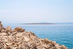 Felsige Küstenlinie und haarscharfes blaues adriatisches Meer mit Inseln Stockfotos