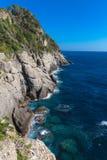 Felsige Küstenlinie und Klippen mit dem Wellenzusammenstoßen Stockbild