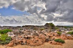 Felsige Küstenlinie und Wolken Stockfotos