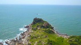 Felsige Klippe auf grüner Insel im blauen Meer und Segelschiff auf Skylineluftlandschaft Brummenansichtklippe auf felsigem Ufer v stock video footage