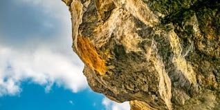 Felsige Klippe auf Hintergrund des blauen Himmels Stockfotografie