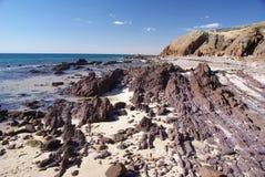 Felsige Schichten auf Strand Lizenzfreies Stockfoto