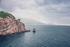 Felsige Seeküste am bewölkten regnerischen Tag Felsen sieht wie Maus mit Käse aus Grauer Himmel mit Regen auf Horizont stockfotografie
