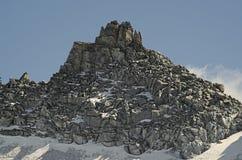 Felsige Spitze mit erstem Schnee Stockbild