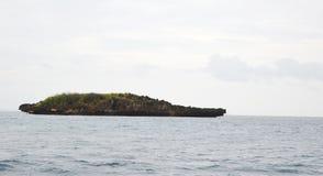 Felsige unbewohnte Inselhochebenenklippe im Ozean mit Wolken, Himmel u. Horizont im Hintergrund Stockfotos