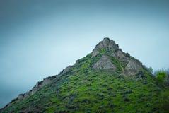 Felsiger Gebirgsspitze mit Gras und Nebel Lizenzfreies Stockfoto