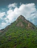 Felsiger Gebirgsspitze mit Gras und Wolken Lizenzfreie Stockfotos