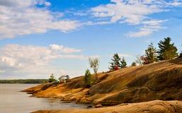 Felsiger Hügel, der von einem See steigt Lizenzfreie Stockbilder
