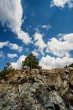 Felsiger Hügel und blauer Himmel mit Wolken lizenzfreie stockbilder