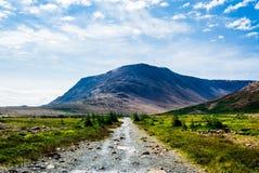 Felsiger Kiesweg, der zu Berg unter Wolken und Himmel führt Lizenzfreies Stockbild