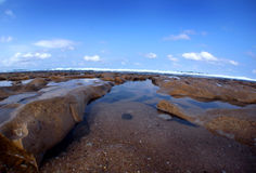 Felsiger Strand bei Ebbe Lizenzfreie Stockfotos