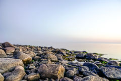 Felsiger Strand bei Sonnenuntergang mit milchigem Wasser Lizenzfreie Stockfotografie