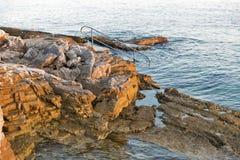 Felsiger Strand des Sonnenuntergangs mit Leiter für das Schwimmen in Istria, Kroatien Stockbilder