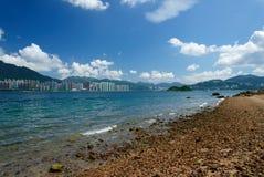 Felsiger Strand mit Gebäude, Wolke und blauem Himmel Stockbild