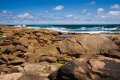 Felsiger Strand mit Wellen im Hintergrund Lizenzfreie Stockbilder