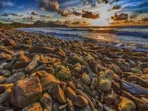 Felsiger Strand am Sonnenuntergang Lizenzfreie Stockfotos