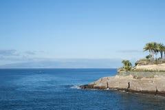 Felsiges Küstengelände durch Casa Del Duque, mit schönen klaren blauen Wasser, früher Morgen, in Adeje-Stadtbezirk, Teneriffa, Sp Lizenzfreie Stockfotografie