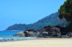 Felsiges Kap und sandiger Strand in den Tropen lizenzfreies stockfoto