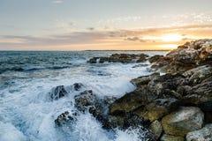 Felsiges Seeufer auf Sonnenuntergang lizenzfreies stockbild