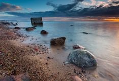 Felsiges Seeufer mit altem Bunker im Meer, langes Belichtungsfoto lizenzfreie stockfotos