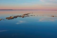 Felsiges Spucken in einem ruhigen See Stockfotos