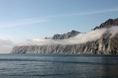 Felsiges Ufer des Ochotsk-Seemorgens Nebels Lizenzfreies Stockfoto