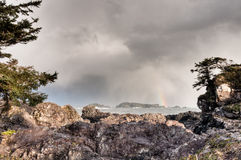 Felsiges Ufer mit entferntem Regenbogen Lizenzfreies Stockfoto
