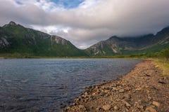 Felsiges Ufer mit grünen Bergspitzen lizenzfreie stockbilder