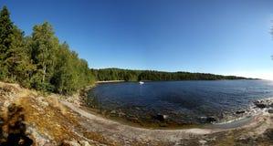 Felsiges Ufer mit Wald Stockfotografie