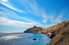 Felsiges Ufer, schöner bewölkter Himmel, die Bucht auf der Küste Schwarzen Meers, Krim, Novy Svet Stockfotos