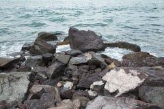 Felsiges Ufer und blaues Wasser Stockfotografie
