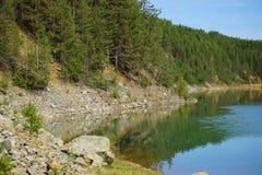 Felsiges Ufer von einem Gebirgssee Lizenzfreie Stockfotos