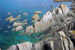 Felsiges Zutageliegen im Ozean Stockfotos