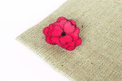 Red felt flower on burlap and white wooden background. Felt brooch idea. Felt hair clips patterns. Felt flower hair clip. Felt hair accessories. Felt accessories stock photography