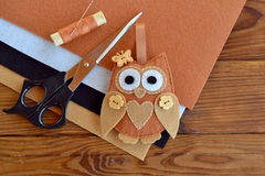 Felt brown owl embellishment. Kids easy art. Toy with wooden buttons. Scissors, thread, needles, felt pieces. Kit for sewing bird toy. Shabby chic. Brown Royalty Free Stock Image