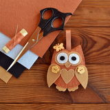Felt brown owl. Shabby chic style. Scissors, felt sheets on a wooden table Stock Images
