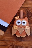 Felt brown owl toy. Shabby chic style. Kids crafts. Felt sheets. Brown wooden table. Close-up Stock Image