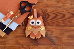 Felt brown owl toy. Shabby chic style. Kids crafts. Scissors, thread, needles, felt sheets - sewing kit. Brown wooden table. Felt ornament. Felt owl decoration royalty free stock photography