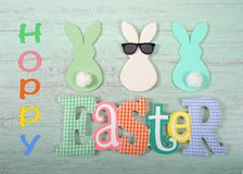 Felt bunnies in earth tone colors in a row Easter sign below. Felt bunnies in earth tone colors in a row, middle bunny wearing fun sunglasses other bunnies royalty free stock photography