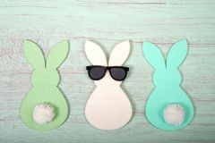 Felt bunnies in earth tone colors in a row on green table. Felt bunnies in earth tone colors in a row, middle bunny wearing fun sunglasses other bunnies bottoms royalty free stock photo