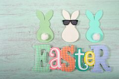 Felt bunnies in earth tone colors in a row Easter sign below. Felt bunnies in earth tone colors in a row, middle bunny wearing fun sunglasses other bunnies royalty free stock photos
